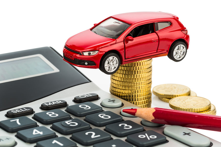 A red car sitting on coins, a calculator, and a red pencil on white background