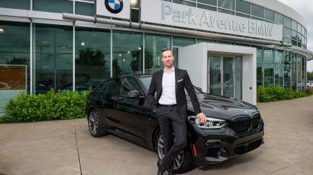 Louis Dupras, directeur général chez Park Avenue BMW et MINI Brossard, devant le concessionnaire Park Avenue BMW